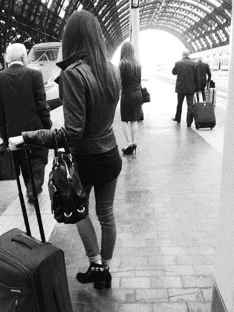 Ragazza con valigia aspetta il treno alla stazione centrale di Milano